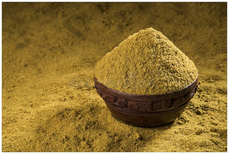 CORIANDER SPICES POWDER GRIND FLAVOUR. INDIAN SPICES CORIANDER POWDER GRIND BOWL WOODEN YELLOW FLAVOUR DHANIYA royalty free stock image