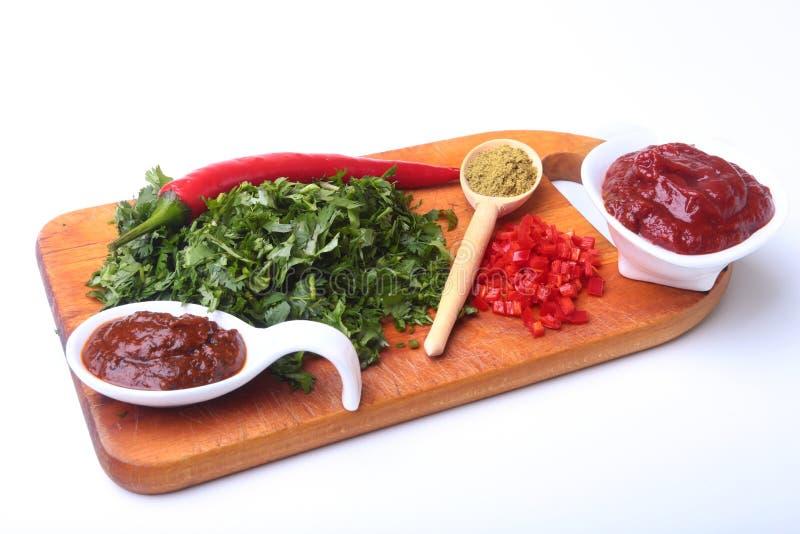 Coriandolo, foglie del coriandolo, passata di pomodoro, peperoncino e spezie verdi freschi su un bordo di legno Ingredienti per c fotografia stock