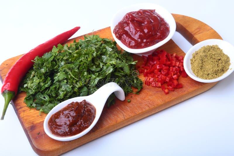 Coriandolo, foglie del coriandolo, passata di pomodoro, peperoncino e spezie verdi freschi su un bordo di legno Ingredienti per c fotografie stock