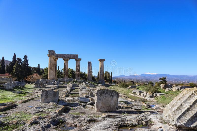 Corinth Greece - Ancient pillars viewed with rubble from ruins in foreground and snow-topped mountains in the distance under a. Very blue sky royalty free stock images