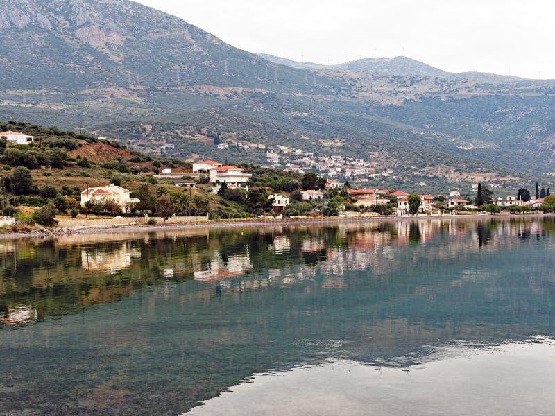 Corinthisch die Golf Visserijdorp in nog Zeewater wordt weerspiegeld stock fotografie