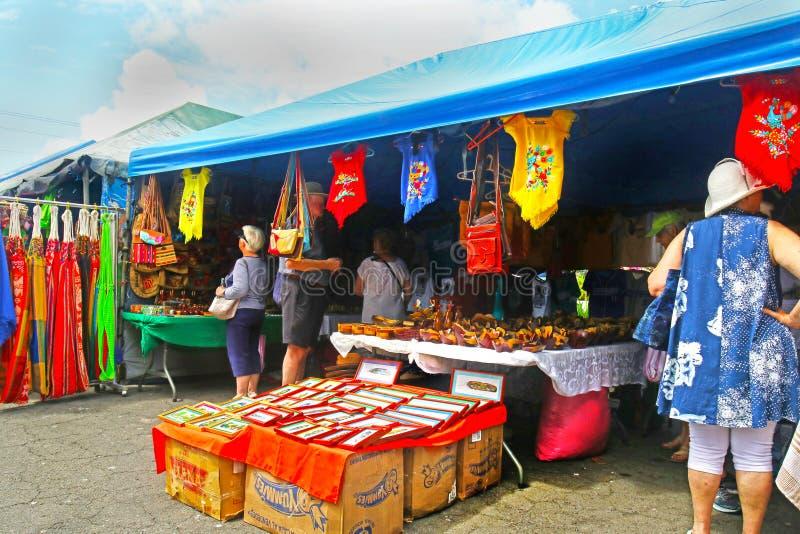Corinto Nicaragua Oktober 10, 2018 Turister som bläddrar på Shops med färgglat gods, kläder, T-skjortor, souvenir royaltyfri fotografi