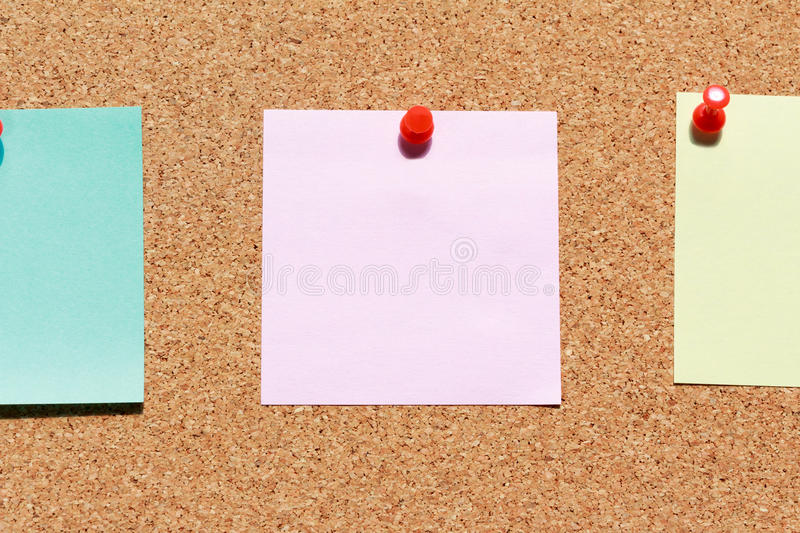 Cork board with colorful blank notes and push pins stock photo
