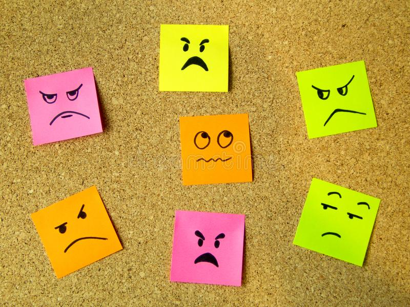 cork board with colorful post its representing various emoticons with anger emotion communication accusing concept stock photos