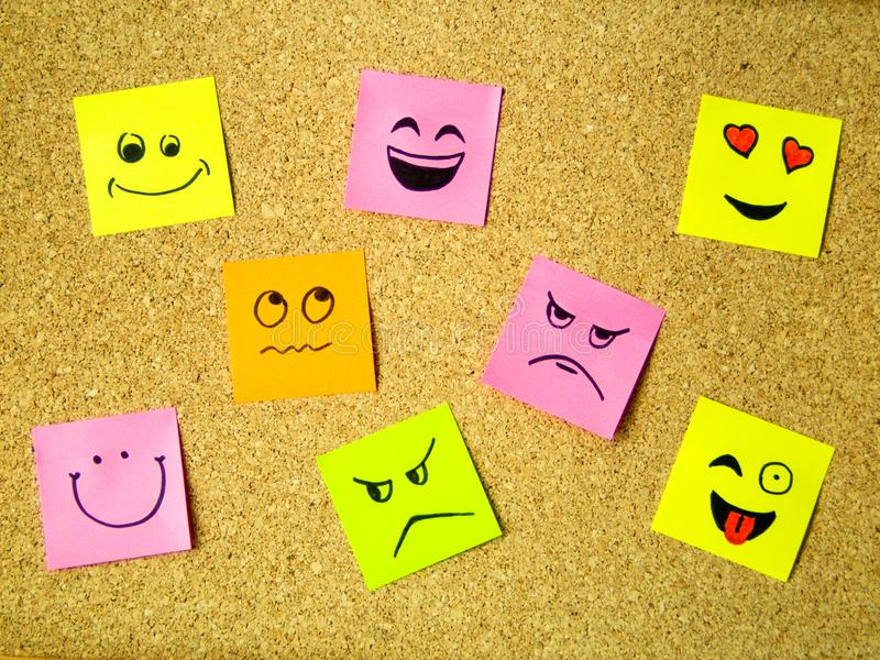 Cork board with colorful post its representing various emoticons with various emotions communication concept. Photo stock images