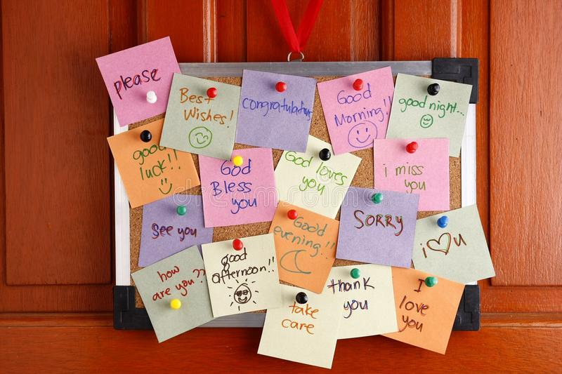 Cork board with messages on colorful papers and push pins hanging by a door. Photo of a Cork board with messages on colorful papers and push pins hanging by a stock image