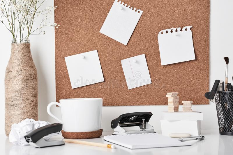 Cork board with office supplies on white background royalty free stock photo