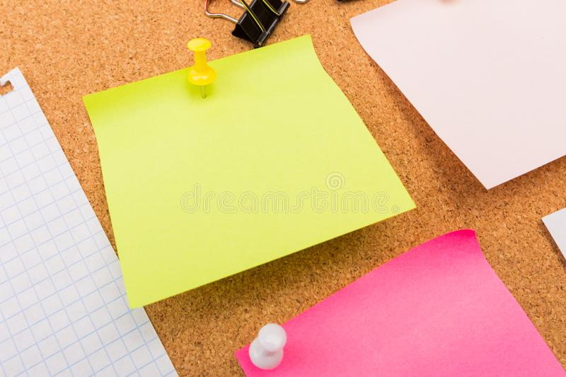 Cork board with pinned colored blank notes - Image stock images