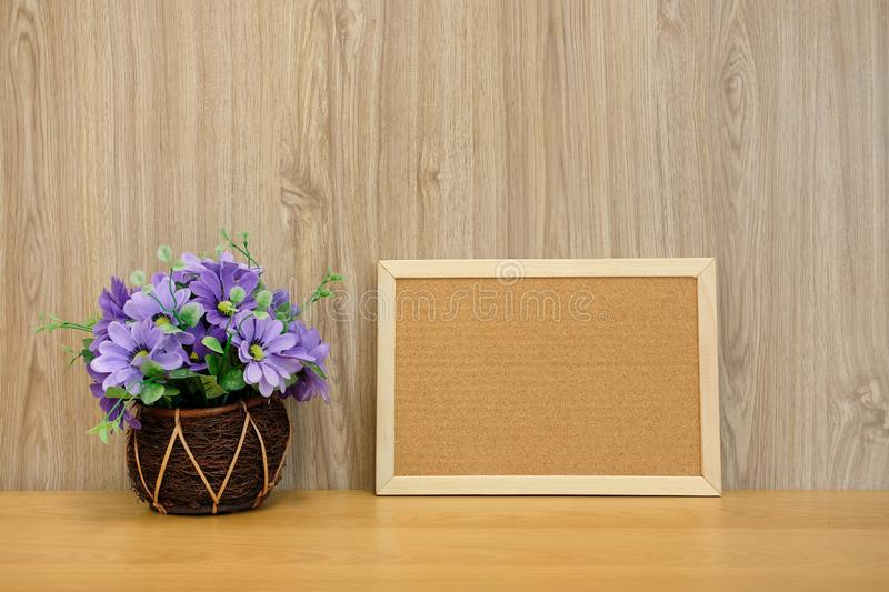 cork board purple artificial flower on wooden table at office stock photos