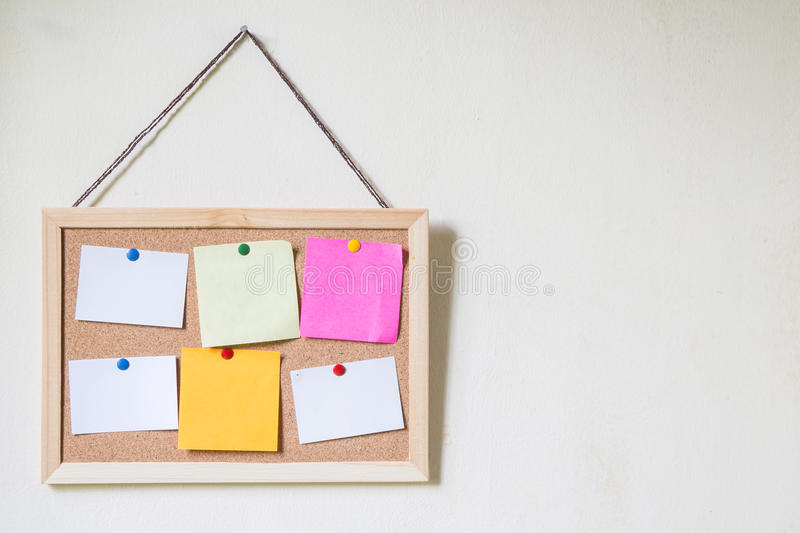 Cork board with several colorful blank notes with pins stock photo