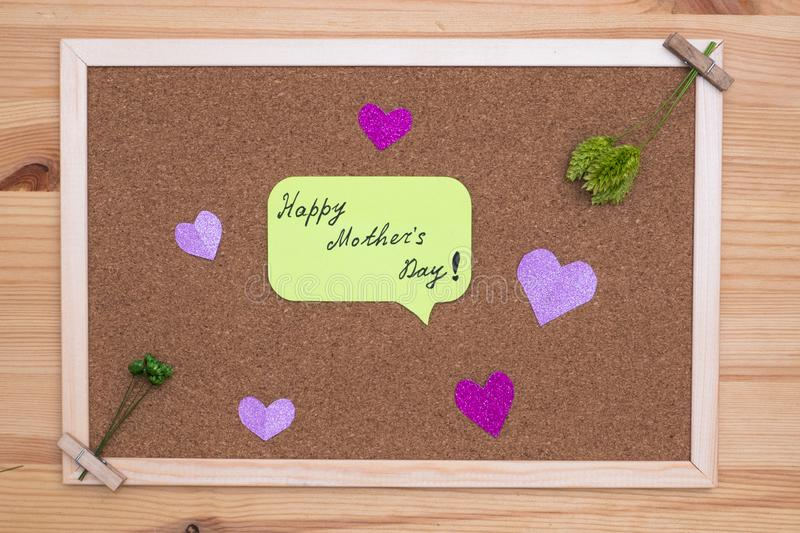 On the cork Board with stickers with the inscription happy mother`s day around the hearts and green flowers stock photo