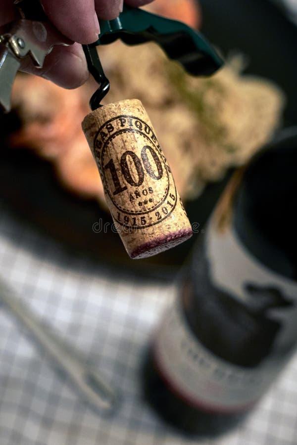 Cork die van de fles rode wijn wordt geschroeft stock fotografie