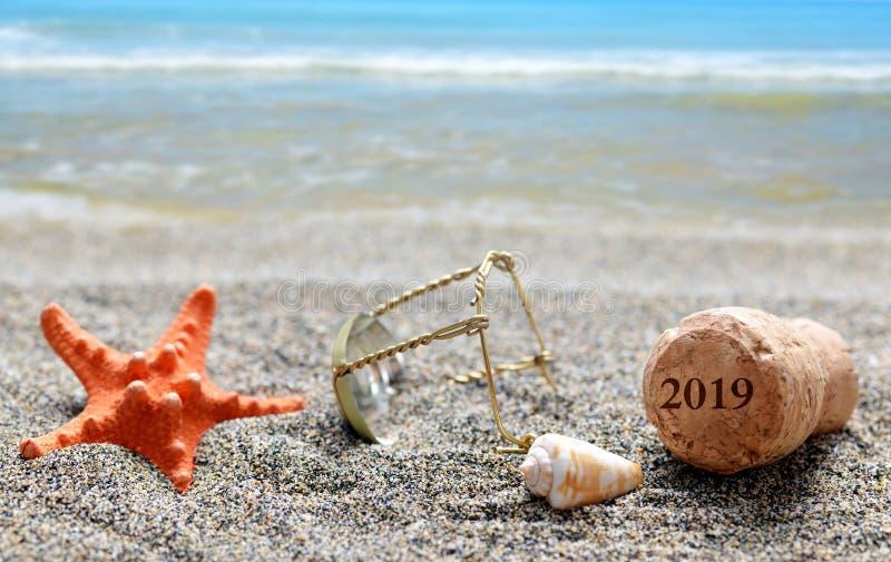 Cork kurk van champagne met nummer 2019 en zeeschelp met zeester op zandstrand royalty-vrije stock afbeeldingen
