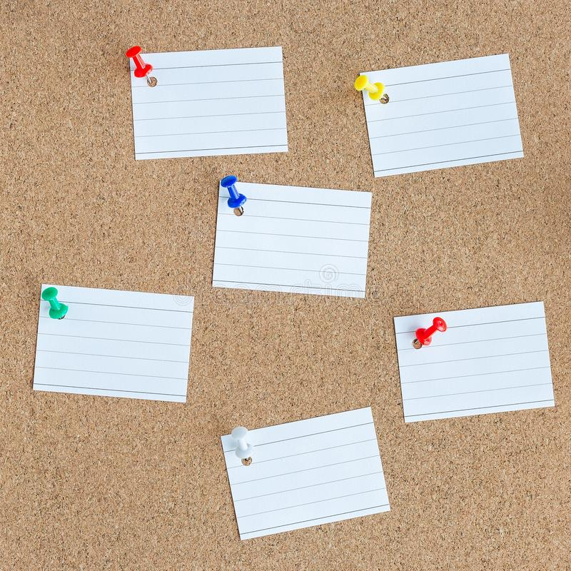 Cork memory board with pinned blank pieces of paper notes, bulletin board, square royalty free stock image