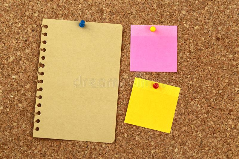 Blank post it notes and paper. Cork notice board with two post it notes (pink and yellow)  pinned to it and a yellow page torn out of a ring binder style note stock photo
