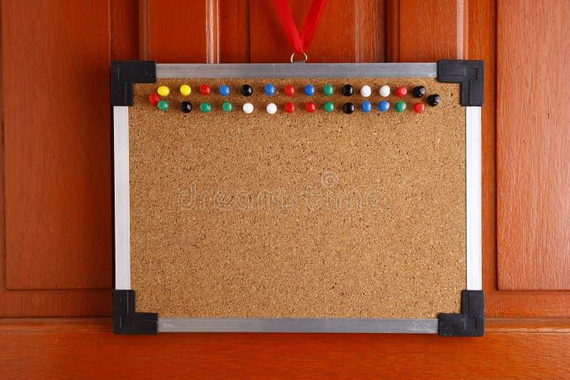 Cork raad met kleurrijke duwspelden die door een deur hangen royalty-vrije stock afbeelding