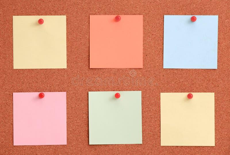 Cork raad met kleurrijke nota's en rode speld stock foto's