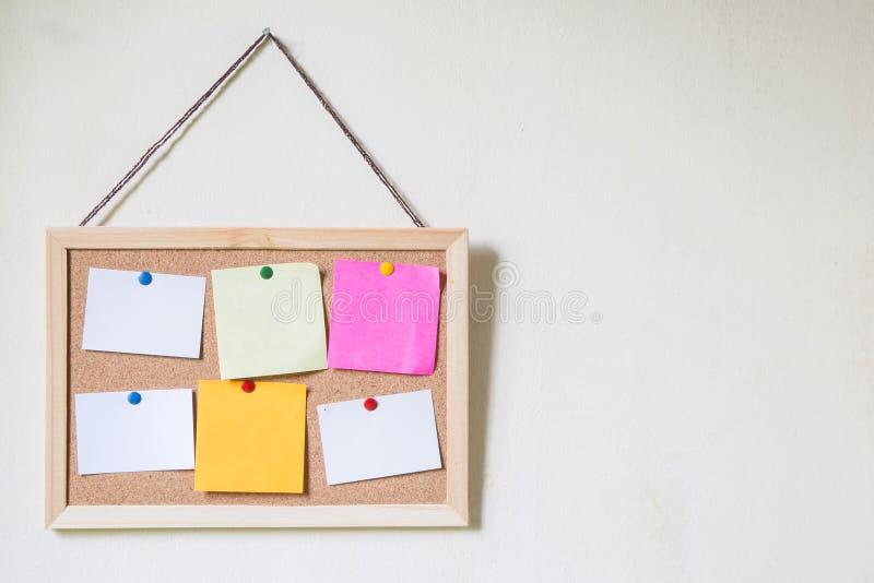 Cork raad met verscheidene kleurrijke lege nota's met spelden stock foto