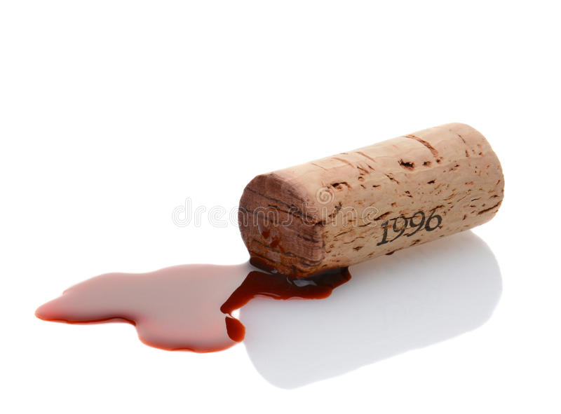 Cork and Red Wine Spill. Closeup of a wine cork and a wine spill on white with reflection. Horizontal format stock images