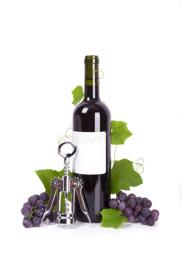 Cork-screw e frasco do vinho vermelho com isolador das uvas fotos de stock