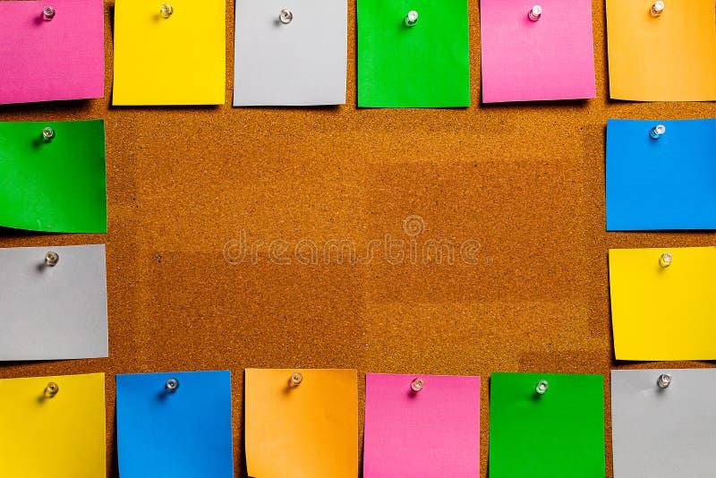 Corkboard/Prikbord door zeer ordelijke geplaatste multicolored stiky type vierkante nota's die volledig wordt gegrenst De nota's  royalty-vrije stock afbeelding