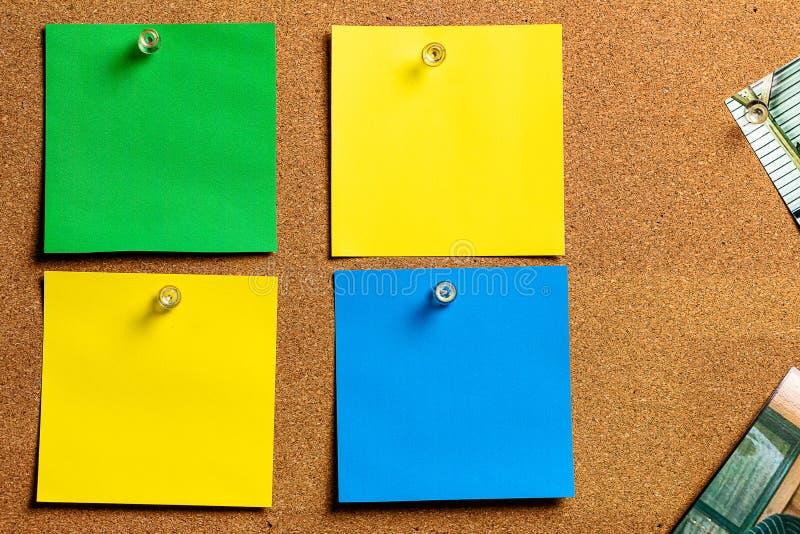 Corkboard/quadro de mensagens e notas pegajosas vazias na forma em ordem amarela, verde e azul, arranjada foto de stock