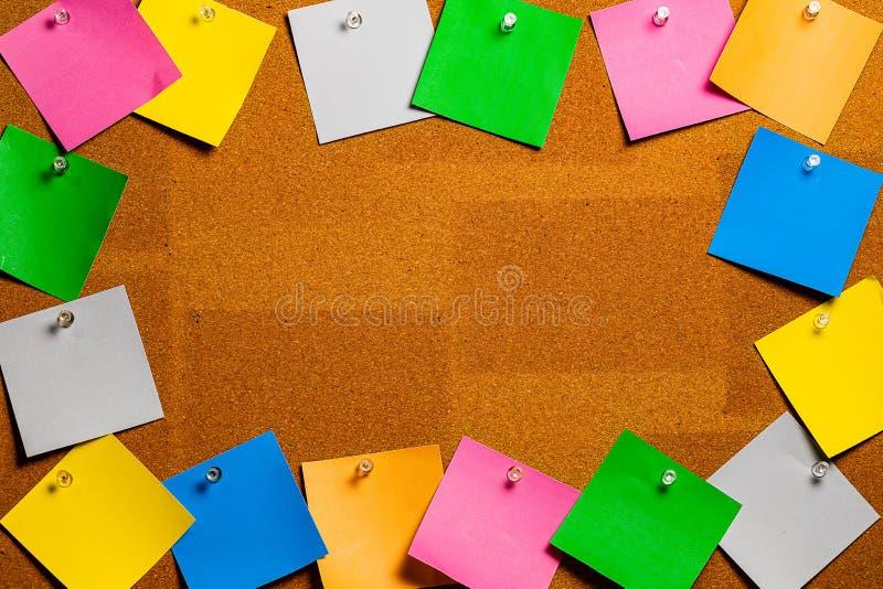 Corkboard, tablica informacyjna/graniczyliśmy całkowicie bardzo bałaganiarskim stubarwnym stiky typem kwadrat notatki Notatki są  fotografia royalty free