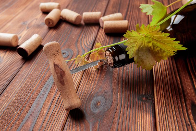 Corkscrew and bottle of wine on the board - Image royalty free stock photography
