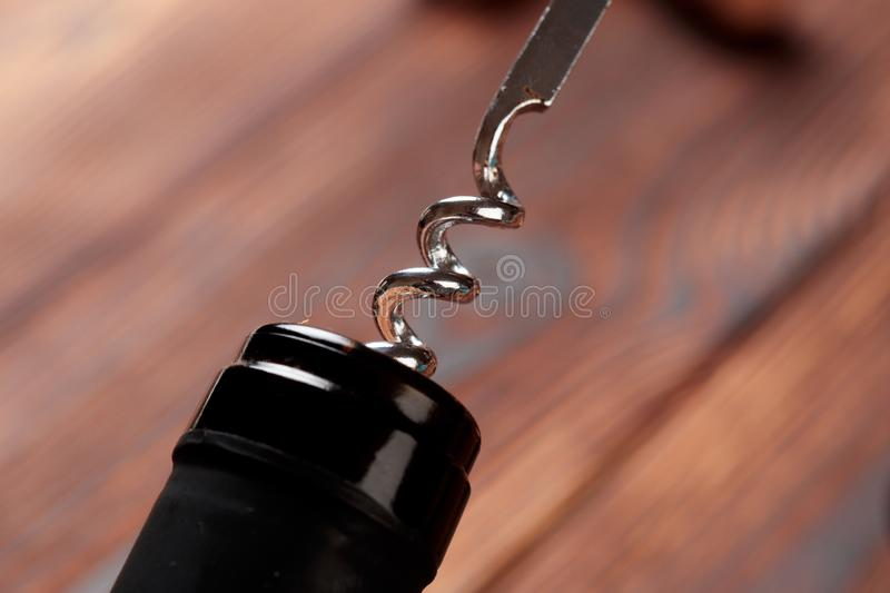 Corkscrew and bottle of wine on the board - Image royalty free stock photo