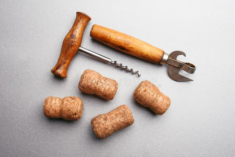 Corkscrew, butelka otwieracz i wino korki na szarym tle zdjęcia royalty free