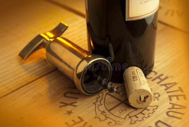 Corkscrew,cork and bottle. A corkscrew,cork and bottle of wine shot on wood crate stock photography