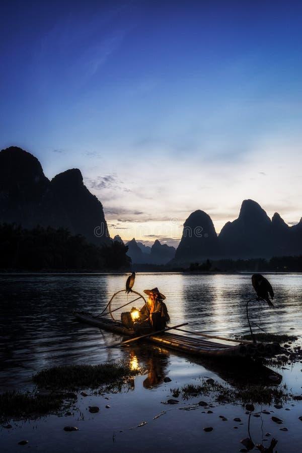 The cormant fisherman in li river. Li river cormant fisherman resting by the famous li river with the 20 yuan bank note scenery on the background. Taken near royalty free stock photo