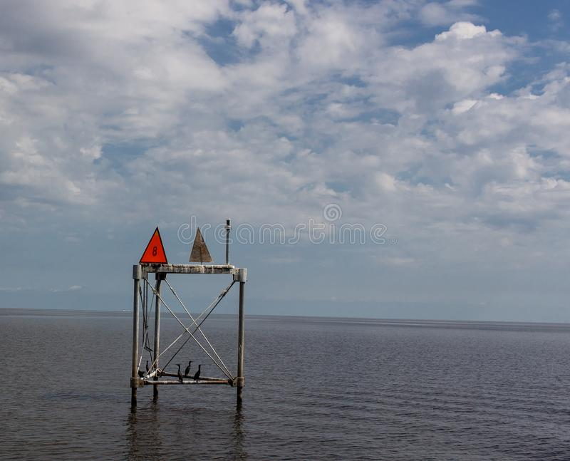 Cormorant`s making good use of a channel Marker on Lake Okeechobee. Broken clouds with blue sky in the background stock photo