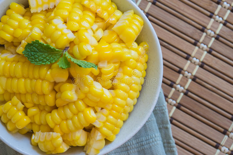 Corn Boil a cup of white bands on the bamboo floor. Corn Boil a cup of white bands on the bamboo floor stock image