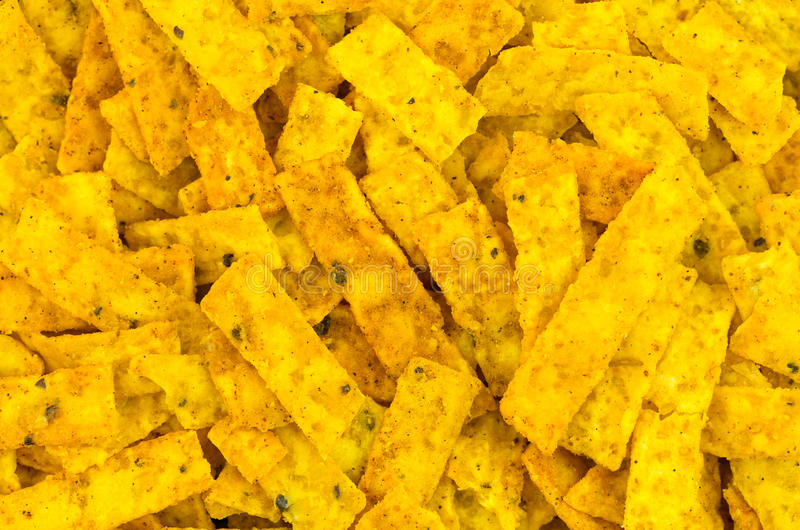Corn chip strips background. Close up of spicey multi grain corn chip strips for taco salads. Though multigrain, they contain saturated fats so not a stock photography