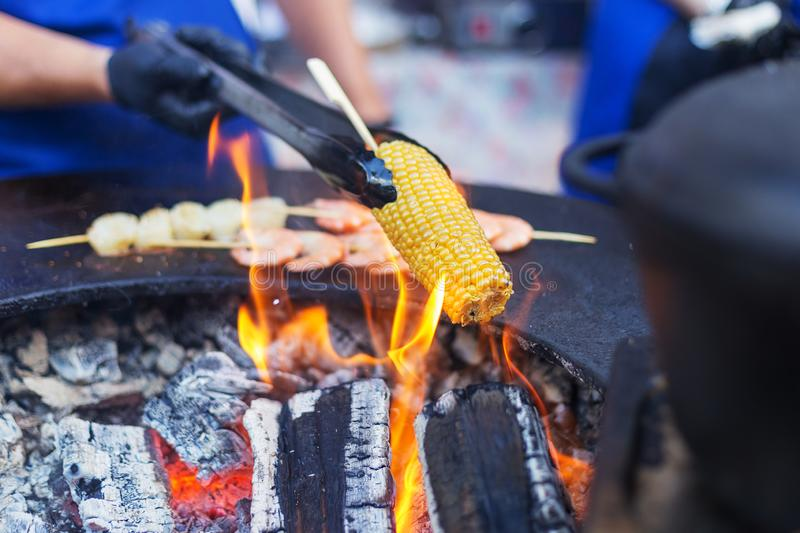 Corn cob on open fire. Concept of street food festival stock images