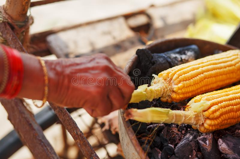Corn cobs on the grill. Close-up image with corns and hands. Asian, Indian and Chinese street food. Trolley on the beach. GOA royalty free stock photo
