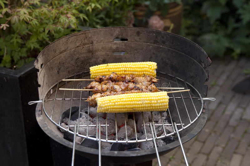 Corn cobs and grilled satay royalty free stock image