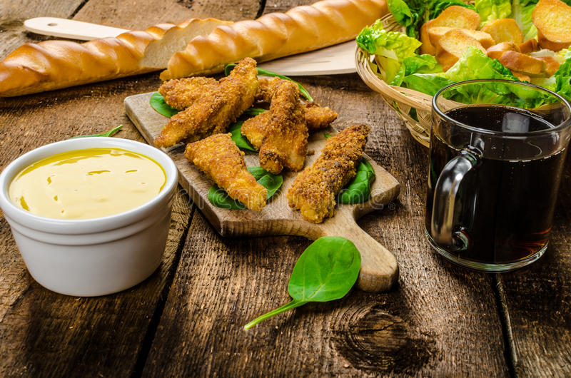 Corn crusted Chicken Tenders. With spinach and toast, honey-dijon mustard dip, homemade bread baguette royalty free stock photography