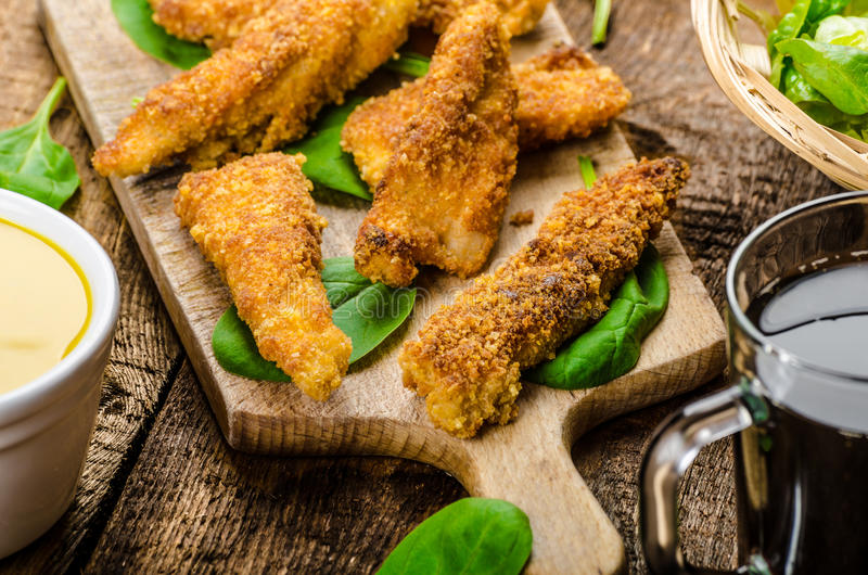 Corn crusted Chicken Tenders. With spinach and toast, honey-dijon mustard dip, homemade bread baguette royalty free stock image