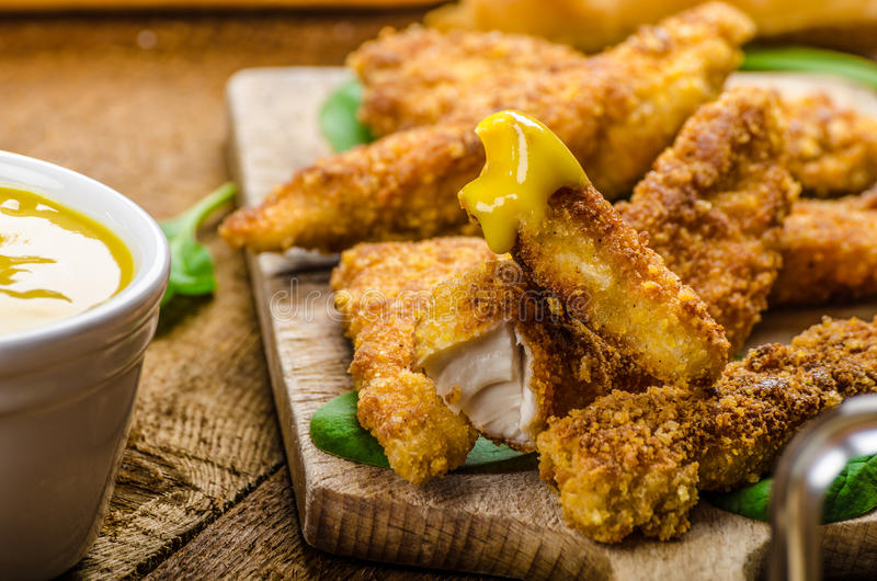 Corn crusted Chicken Tenders. With spinach and toast, honey-dijon mustard dip, homemade bread baguette stock photography