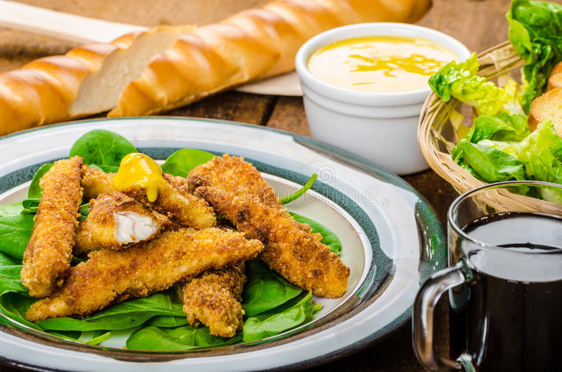 Corn crusted Chicken Tenders. With spinach and toast, honey-dijon mustard dip, homemade bread baguette stock images