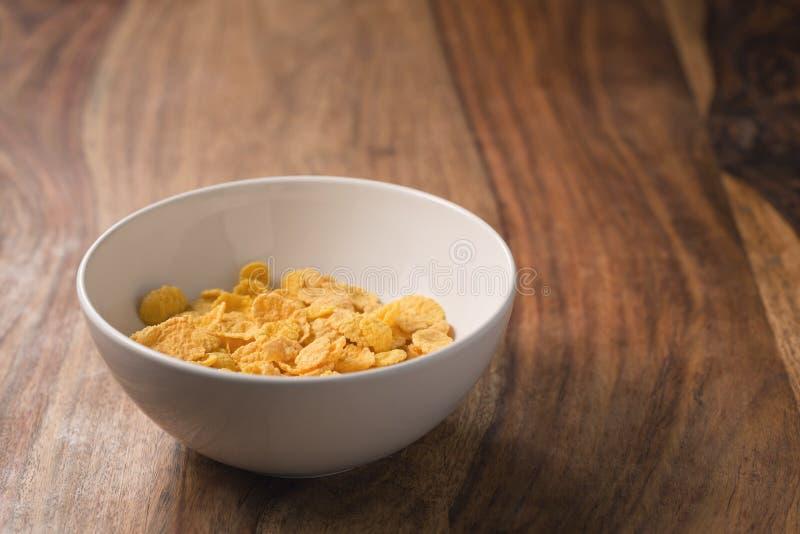 Corn Flakes in der weißen Schüssel auf Tabelle stockbild
