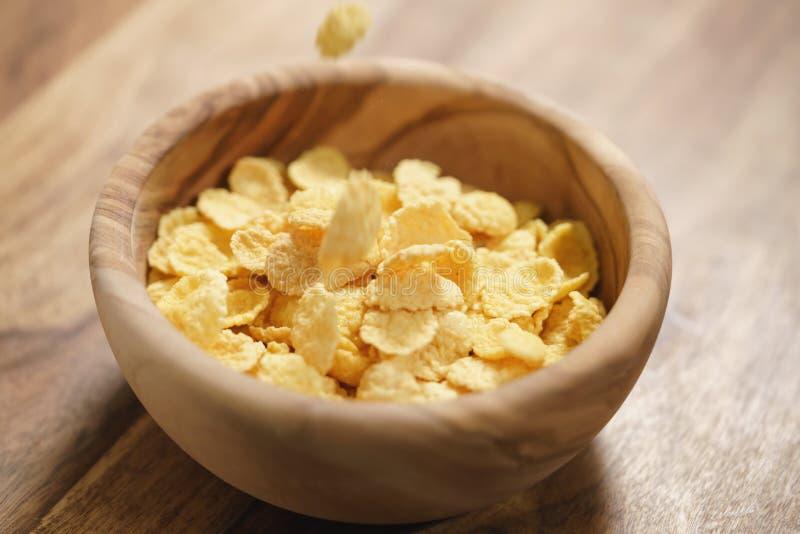 Corn Flakes, die in hölzerne Schüsselnahaufnahme fallen lizenzfreies stockfoto