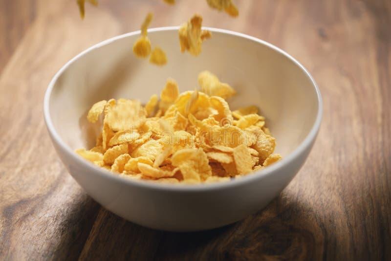 Corn Flakes, die in weiße Schüssel auf Tabellennahaufnahme fallen stockbilder
