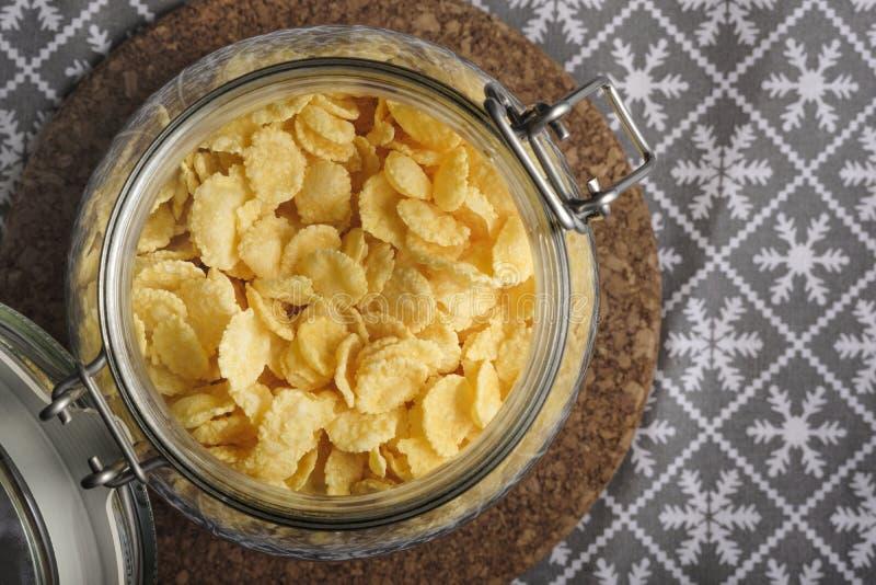 Corn-Flakes in einem Glasgefäß auf dem Tisch, Stillleben, im Konzeptfrühstück lizenzfreies stockfoto
