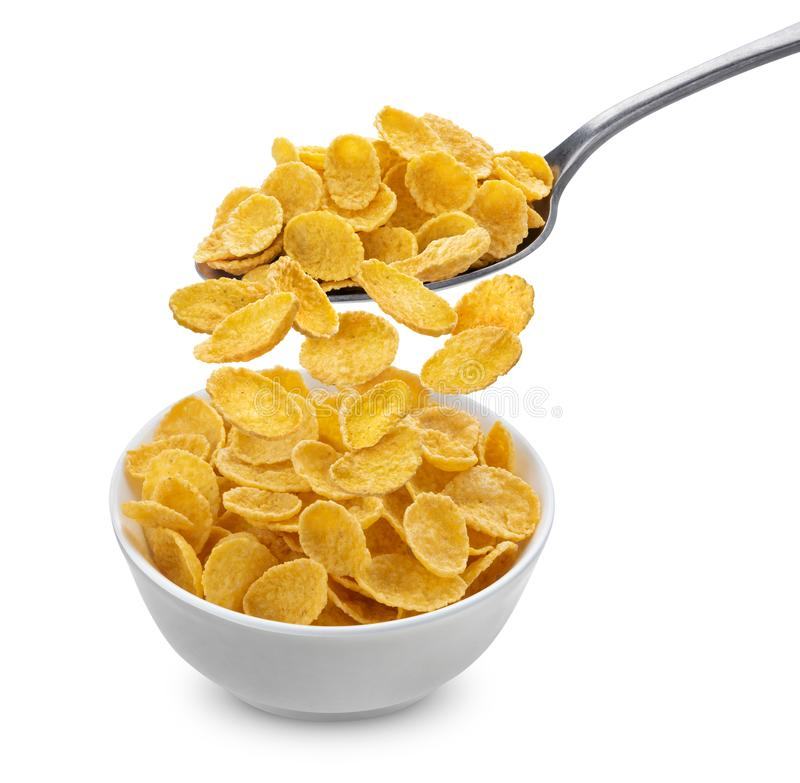 Corn flakes falling from spoon into bowl isolated on white background. Corn flakes falling from spoon into ceramic bowl isolated on white background with stock photo