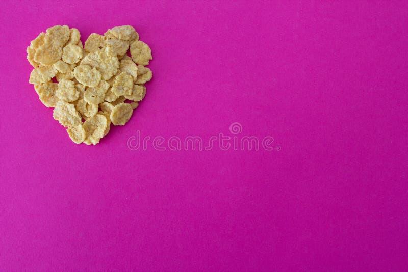 Corn Flakes in Form von Herzen auf einem rosa Hintergrundgetreide lizenzfreie stockfotografie