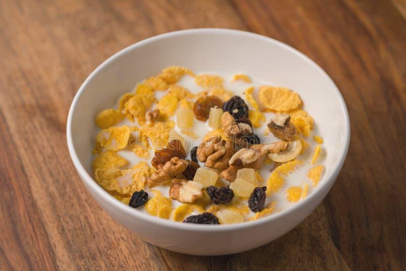 Corn Flakes mit Nüssen und Früchten in der weißen Schüssel auf hölzerner Tabelle lizenzfreie stockbilder