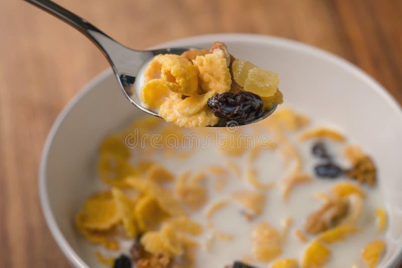 Corn Flakes mit Nüssen und Früchten in der weißen Schüssel auf hölzerner Tabelle lizenzfreies stockbild